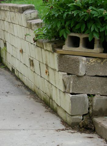 collapsing retaining wall with severe damage in Ely