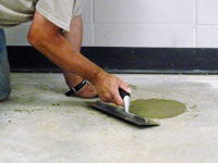 Repairing the cored holes in the concrete slab floor with fresh concrete and cleaning up the Virginia home.