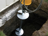 Installing a helical pier system in the earth around a foundation in Cloquet