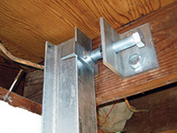 Securing the i-beam system to the top of the floor joist in a foundation wall repair in Virginia.