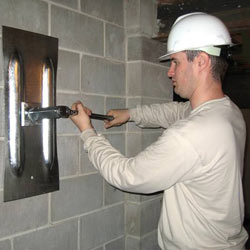installing a wall anchor to repair an bowing foundation wall in Ashland